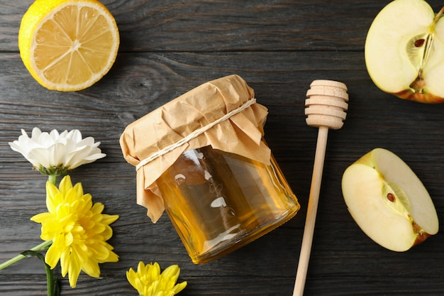 北斗七星、リンゴ、レモン、花、木製の背景の上に蜂蜜が付いている瓶