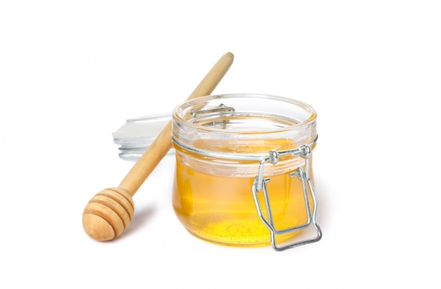Dipper and glass jar with honey isolated on white