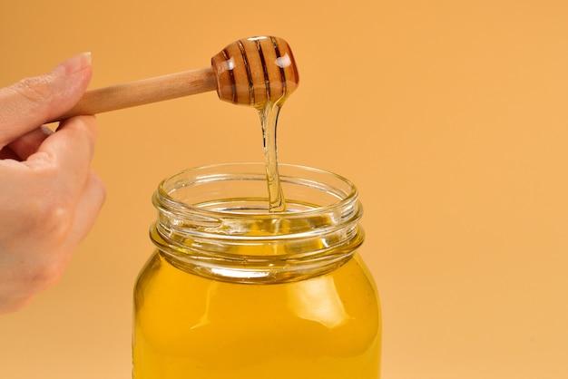 Диппер с медом в руке женщины на оранжевом фоне. место для текста или дизайна.