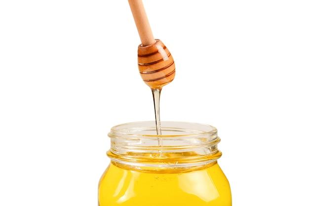 女性の手に蜂蜜とディッパー。テキストやデザインのためのスペース。