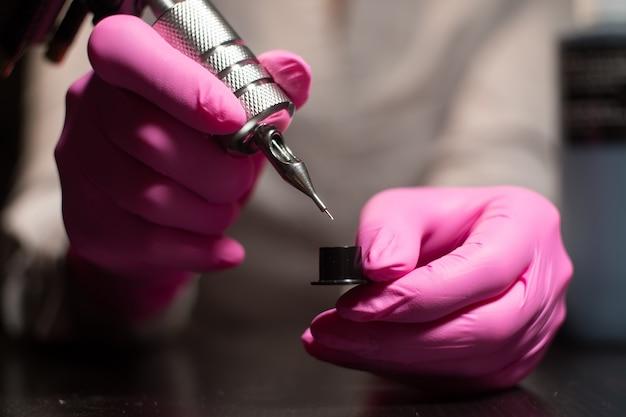 タトゥーマシンのペンキに針を浸す