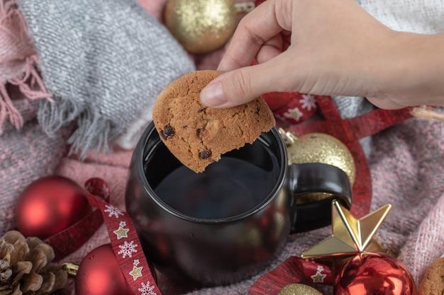 Immergere il biscotto allo zenzero nella bevanda sul tavolo ricoperto di ornamenti natalizi