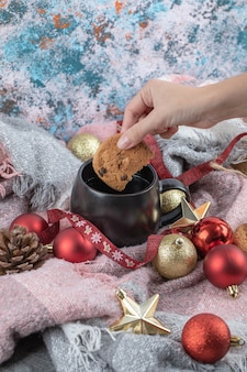 Dipping ginger cookie into drink on the table covered with christmas ornaments