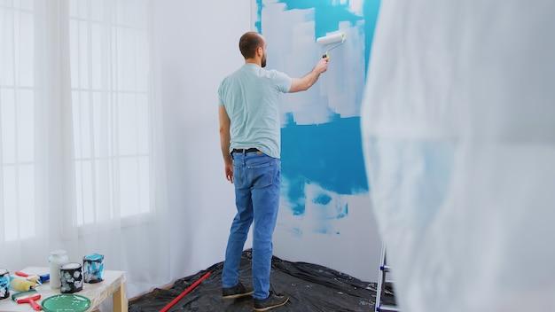 롤러 브러시를 페인트에 담그십시오. 홈 리노베이션, 핸디맨 리노베이션. 개조 및 개선하는 동안 아파트 재장식 및 주택 건설. 수리 및 장식.