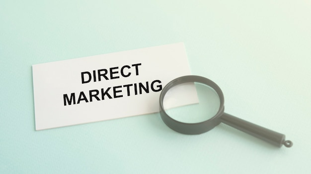 Direct marketing word on white paper card and magnifying lens
