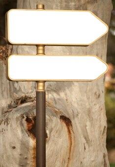 背景に幻想的な木と方向指示看板
