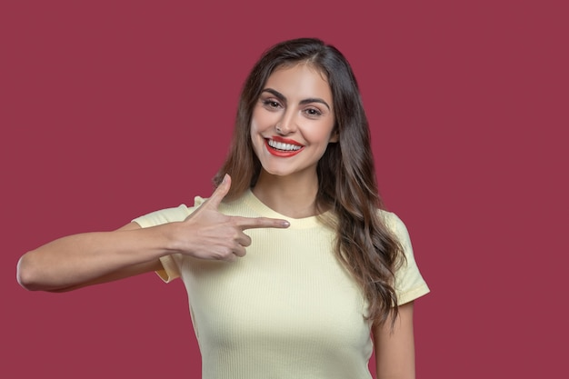 Direction, to side. joyful young dark-haired woman with makeup pointing her finger to side holding her hand at shoulder level