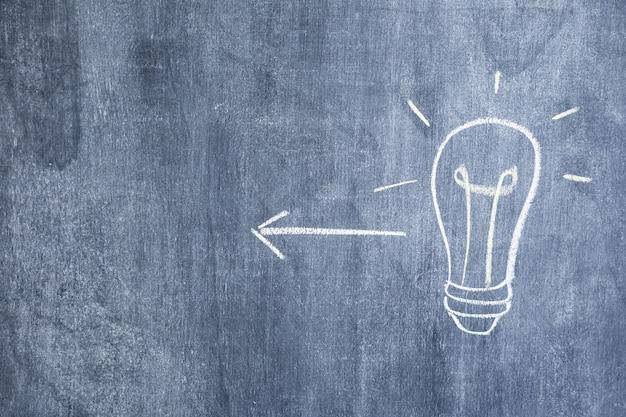 電球がチョークで描かれた方向性の矢印