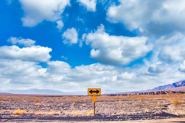 아름다운 푸른 하늘과 넓은 수평선이 있는 사막의 방향 표지판. 여행, 자유, 휴가 및 교통에 대한 개념입니다.