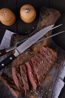 スライスしたビーフステーキの真上にスパイスを添えて。まな板の上で調理された食品