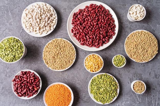 真上には、灰色の背景上のエンドウ豆、レンズ豆、豆、マメ科植物の品揃え。