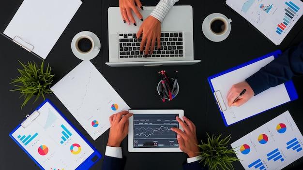 재무 문서 및 프레젠테이션 작업을 사무실 책상에서 태블릿으로 작업하는 비즈니스 사람들의 바로 위, 프로젝트 메모 작성