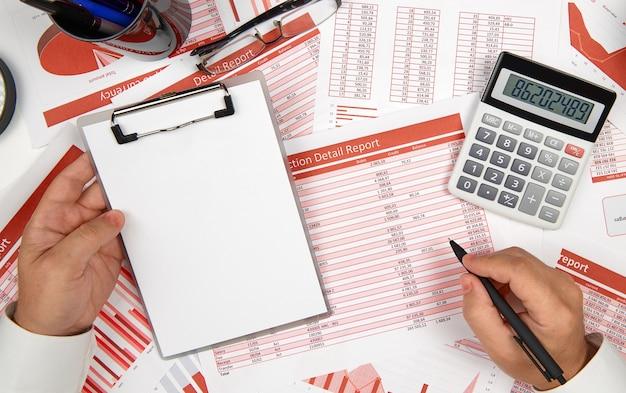 Прямо над представлением бизнесмена, работающего и считающего финансы, читает и пишет отчеты. концепция финансового учета бизнеса.