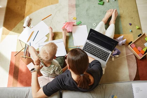 Прямо над изображением многозадачной матери, сидящей на полу во время работы и одновременного рисования с сыном