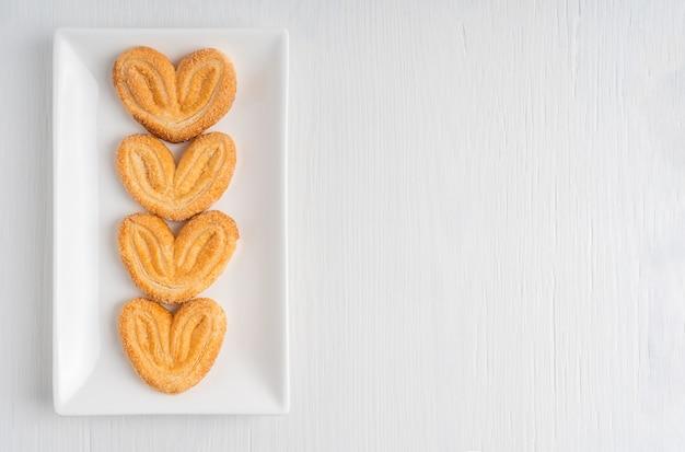 Прямо над видом на сладкие домашние пальмовые четыре печенья в форме сердца, лежащие на тарелке на столе