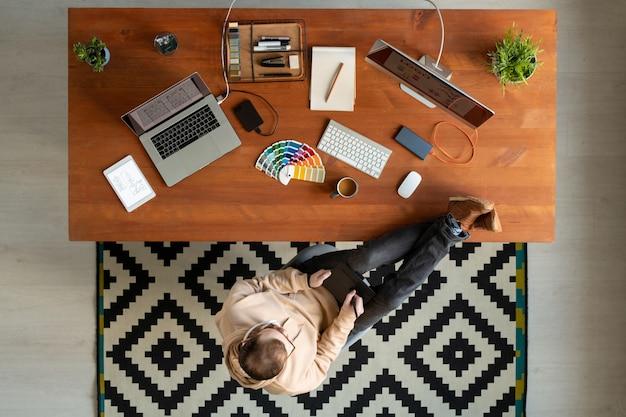 テーブルの上に足を保ち、グラフィックデザインに取り組んでいる間描画パッドを使用して若い男のビューの真上