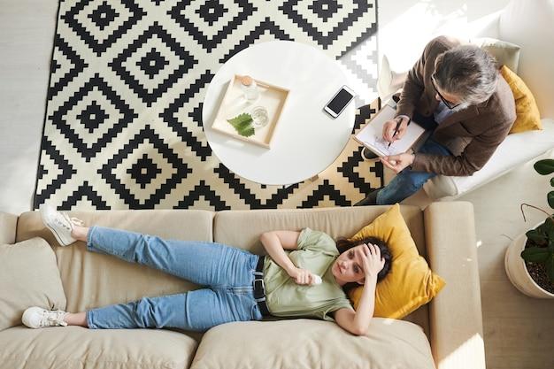 심리 치료 세션 동안 소파에 누워 있는 쾌활한 젊은 여성의 위에서 직접 찍은 사진