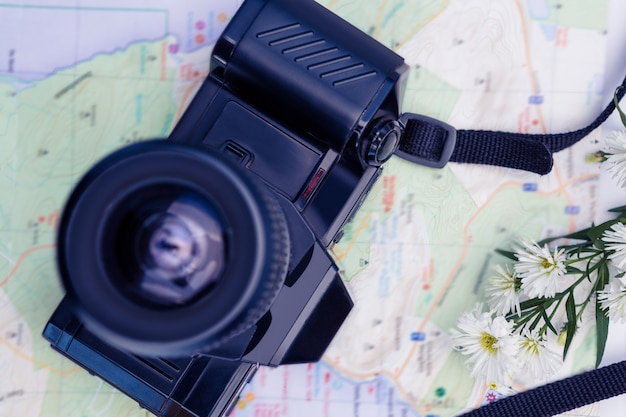 Directly above shot of digital camera and map and flowers on table