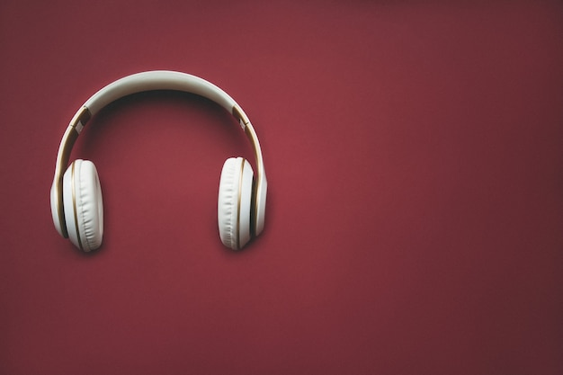 Directly above shot of headphones over red background. music concept. minimal concept.