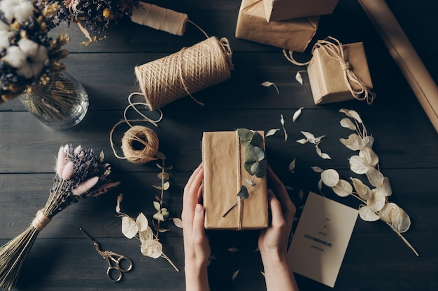 Directly above view of woman packing gifts into kraft paper using twig for decoration in store