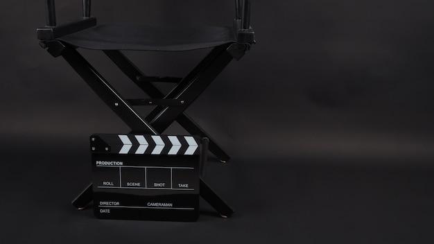 ディレクターズチェアと黒のカチンコまたは映画のスレートは、黒の背景でビデオ制作、映画、映画、映画産業で使用されます。