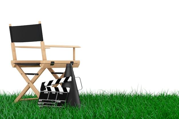 ディレクターズチェア、映画の鳴子と白い背景の草の上のメガホン。 3dレンダリング