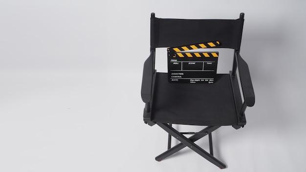 흰색 배경에 검정색 및 노란색 클래퍼 보드 또는 영화 슬레이트가 있는 감독 의자는 비디오 제작 및 영화 산업에 사용됩니다.