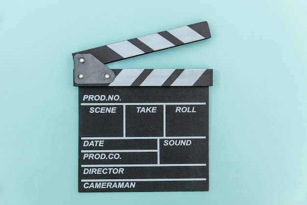 Director empty film making clapperboard or movie slate isolated on blue background