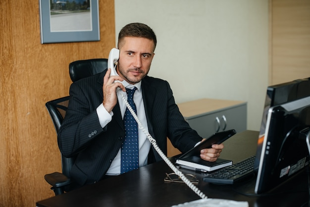 The director is talking in the office by phone. business