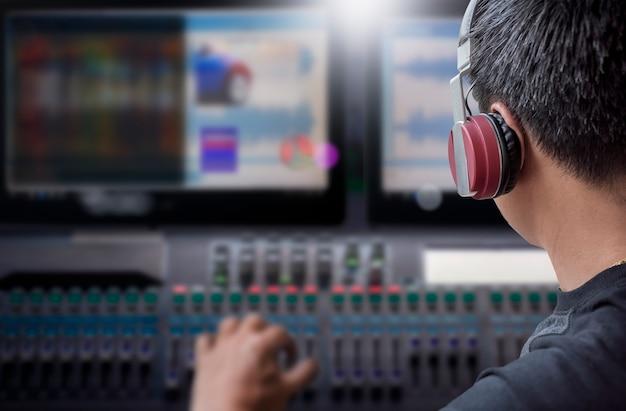 Режиссер с наушниками, работающими на видео и звуковой микшерной консоли в студии