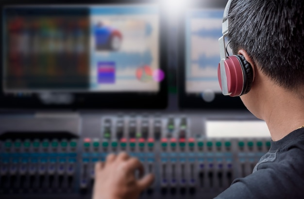 Director with headphone working on video and sound mixing console in the studio