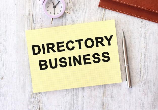 나무 작업 테이블에 누워 노트북에 쓰여진 directory business 텍스트