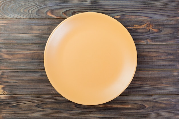 Directy above empty orange matte plate on dark wood