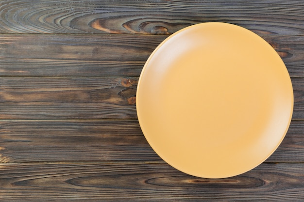 Directy above empty yellow matte dish for dinner on dark wooden background with copy space