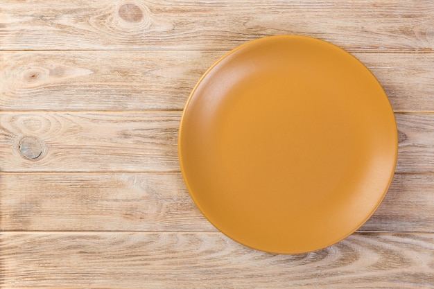 Directy above empty yellow matte dish for dinner on orange wooden background with copy space