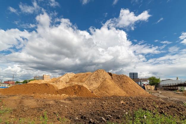 Курган грязи на фоне голубого неба с белыми облаками. Premium Фотографии