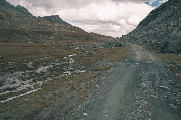 Dirt mountain road with dramatic stormy sky and panoramic view.