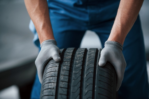 바퀴에 먼지. 수리 차고에서 타이어를 들고 정비공. 겨울 및 여름 타이어 교체