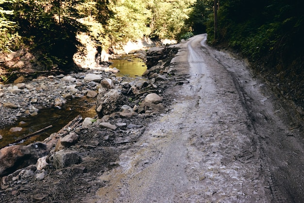 Dirt road after rain. fragment of car off-road with autumn nature wet muddy of backcountry countryside.