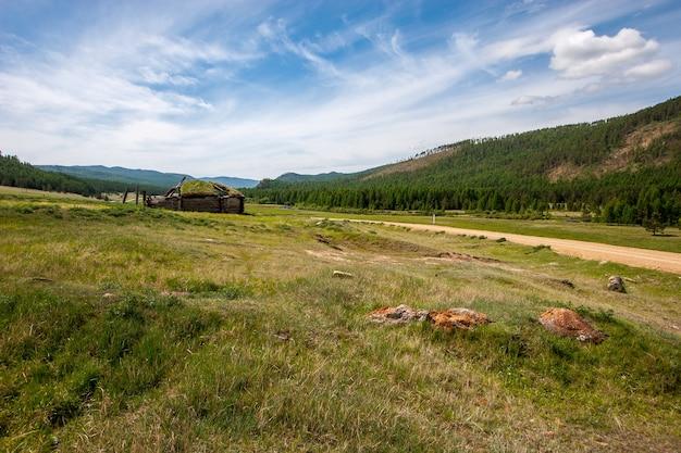 丘と草の小屋が生い茂った廃墟の古いパオの間の未舗装の道路