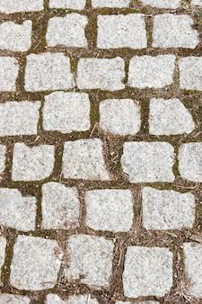 パターンを形成する花崗岩の石のブロックで飾られた未舗装の道路