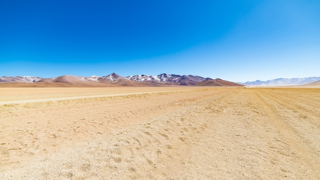 Dirt road at high altitude with sandy desert and barren volcano range on the andean highlands