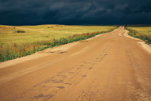 Dirt road to the horizon line under dramatic dark storm clouds.