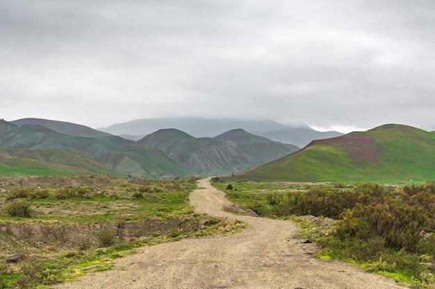 Грунтовая дорога в гористой местности в пасмурную погоду