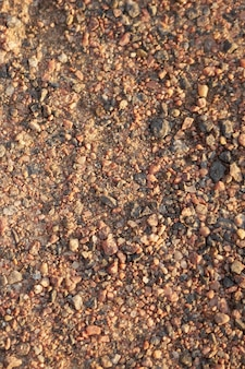 Dirt road made of small granite stones as a background.