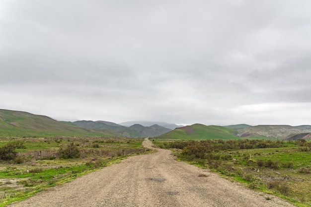 Dirt road in a mountainous area in cloudy weather