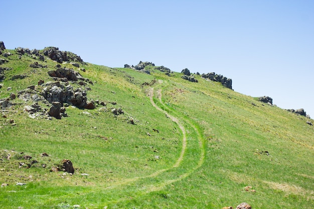 青空の下、山頂に沿って走る未舗装の道路