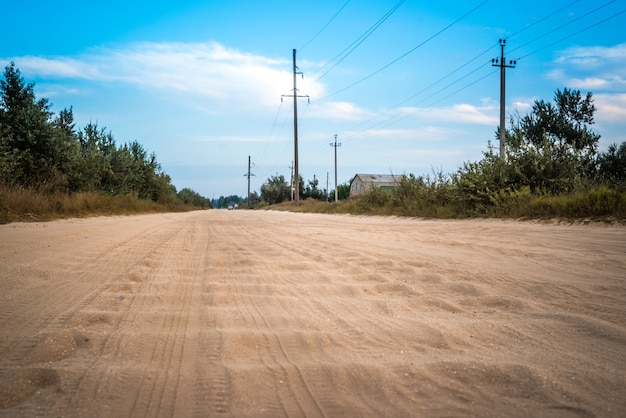 Dirt road with a sandy waves, cloud covering the blue sky