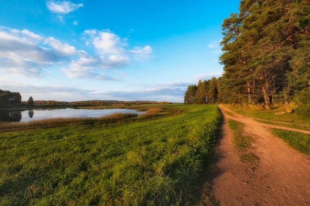이른 가을의 아름다운 저녁에 숲과 호수 사이의 흙 마을 도로. 푸쉬킨 산맥, 프스코프 지역, 러시아.