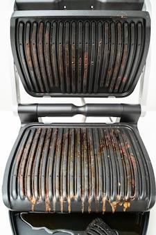 蓋を開けて電気グリルを調理した後、汚れた。日常生活で調理するための器具。ステンレス鋼製、特殊な焦げ付き防止コーティング。健康食品。油脂を含まない食品。